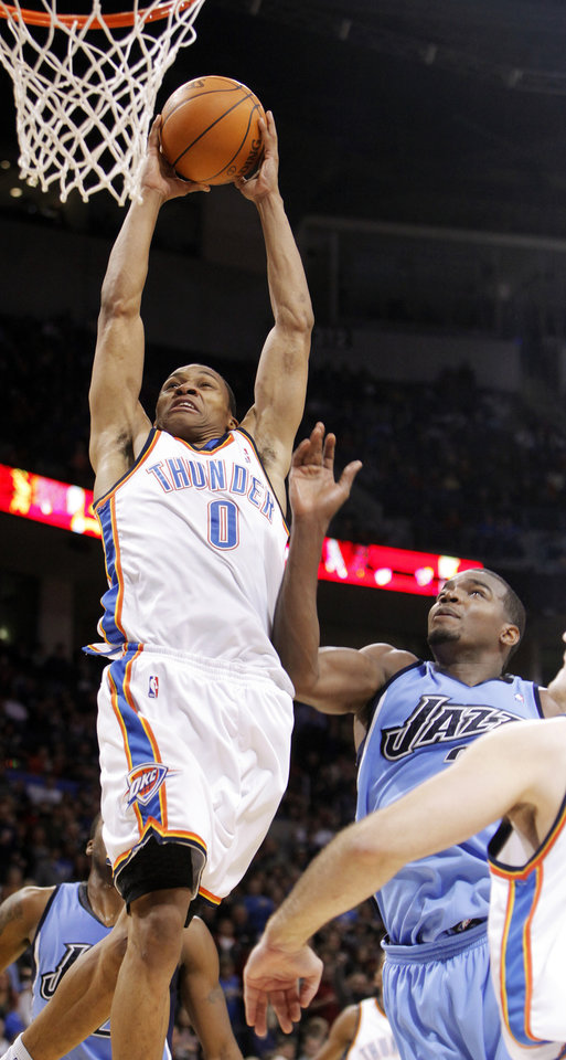 Photo - Oklahoma City's Russell Westbrook (0) dunks the ball in front of Paul Millsap (24) of Utah in the fourth quarter during the NBA basketball game between the Oklahoma City Thunder and the Utah Jazz at the Ford Center in Oklahoma City, Thursday, December 31, 2009. The Thunder won, 87-86. Photo by Nate Billings, The Oklahoman