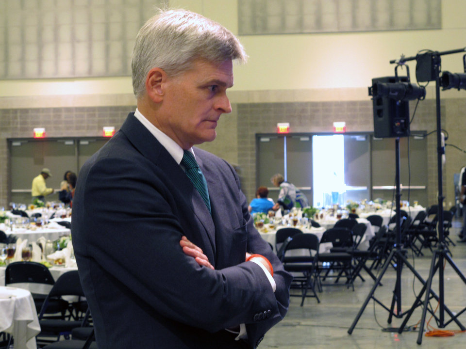 Photo - Republican U.S. Rep. Bill Cassidy speaks to a local elected official about his campaign for Louisiana's U.S. Senate seat after talking at the Louisiana Municipal Association's annual convention on Saturday, Aug. 2, 2014, in Baton Rouge, La. Cassidy is running against three-term Democratic incumbent Sen. Mary Landrieu. (AP Photo/Melinda Deslatte)