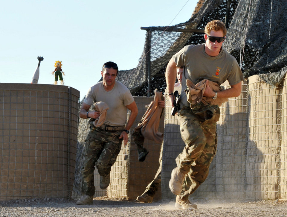 Photo - FILE - In this Nov. 3, 2012 file photo, Britain's Prince Harry, right, or just plain Captain Wales as he is known in the British Army, races out from the VHR (very high readiness) tent to scramble his Apache with fellow pilots, during his 12-hour shift at the British-controlled flight-line in Camp Bastion southern Afghanistan. During Prince Harry's 20-week deployment in Afghanistan, he served as an Apache helicopter pilot with the Army Air Corps. (AP Photo/ John Stillwell, Pool, File)