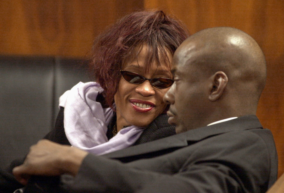 FILE - In this Nov. 25, 2002, file photo, singer Whitney Houston, left, smiles at her husband, singer Bobby Brown, during a court hearing  in Dekalb County State Court in Decatur, Ga. Publicist Kristen Foster said, Saturday, Feb. 11, 2012, that singer Whitney Houston has died at age 48.  (AP Photo/Erik S. Lesser, File) ORG XMIT: NY206