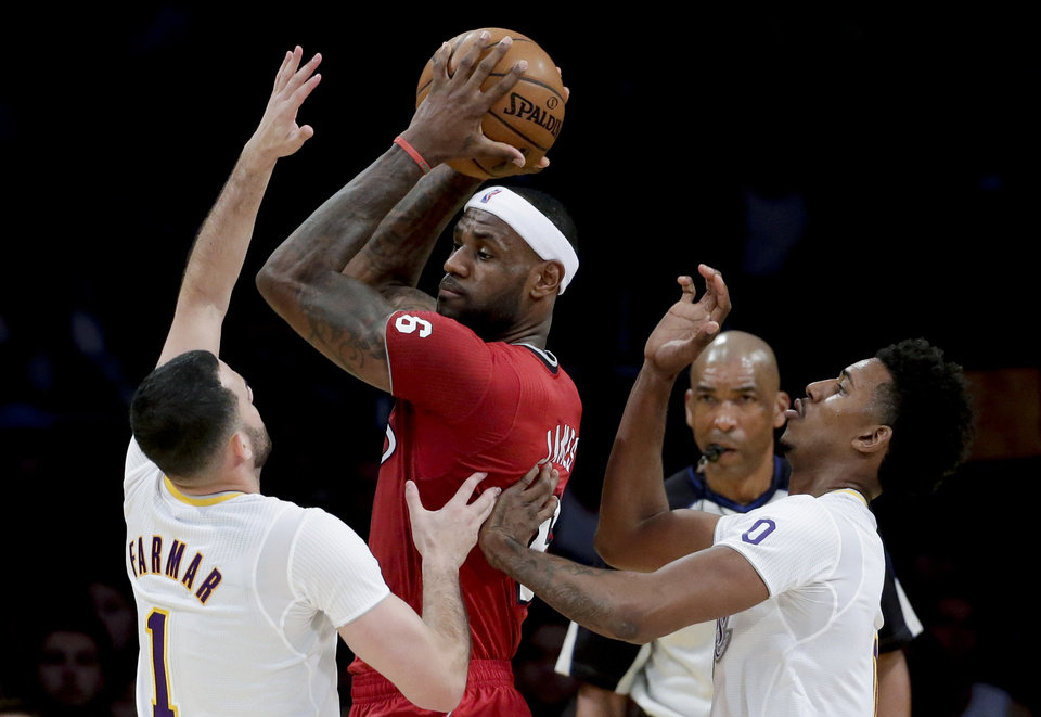 Photo - Miami Heat forward LeBron James, middle, is double-teamed by Los Angeles Lakers' Jordan Farmar, left, and Nick Young during the first half of an NBA basketball game in Los Angeles, Wednesday, Dec. 25, 2013. (AP Photo/Chris Carlson)