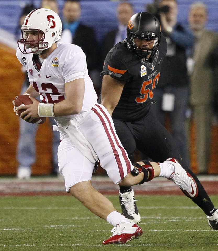 Photo - Stanford quarterback Andrew Luck (12) scrambles as Oklahoma State defensive end Jamie Blatnick pursues during the first half of the Fiesta Bowl NCAA college football game Monday, Jan. 2, 2012, in Glendale, Ariz. (AP Photo/Matt York)