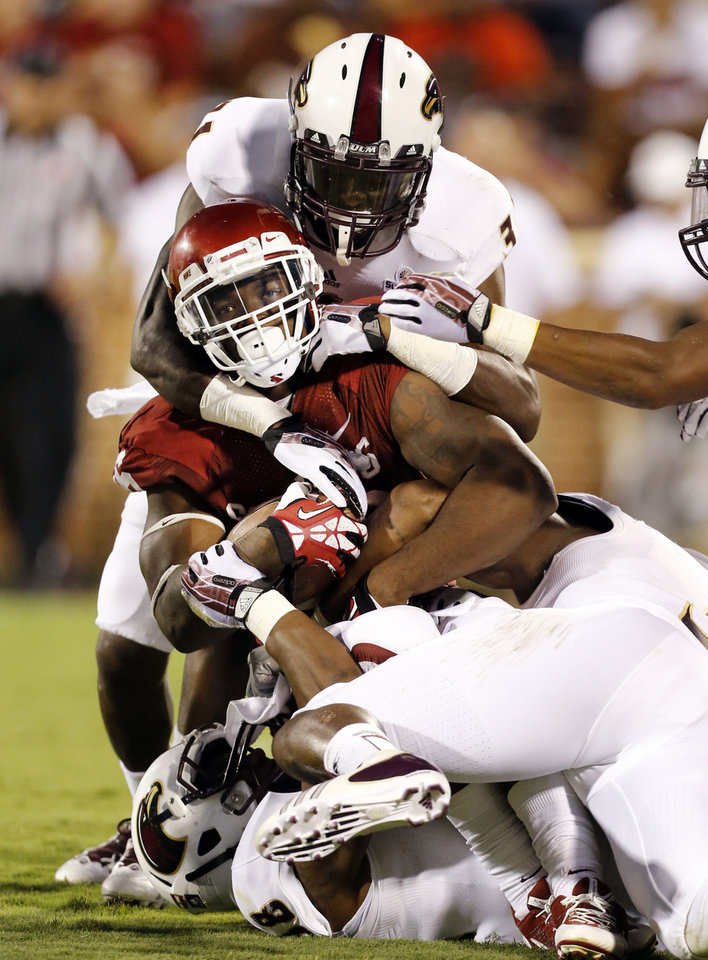 Photo - Damien Williams (26) is brought down during the second half of the college football game where the University of Oklahoma Sooners (OU) play the University of Louisiana Monroe Warhawks at Gaylord Family-Oklahoma Memorial Stadium in Norman, Okla., on Saturday, Aug. 31, 2013. Photo by Steve Sisney, The Oklahoman