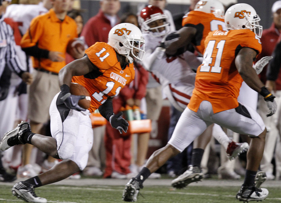 Photo - Oklahoma State's Shaun Lewis (11) returns an interception that was tipped to him by Brodrick Brown during the Bedlam college football game between the University of Oklahoma Sooners (OU) and the Oklahoma State University Cowboys (OSU) at Boone Pickens Stadium in Stillwater, Okla., Saturday, Nov. 27, 2010. Photo by Chris Landsberger, The Oklahoman