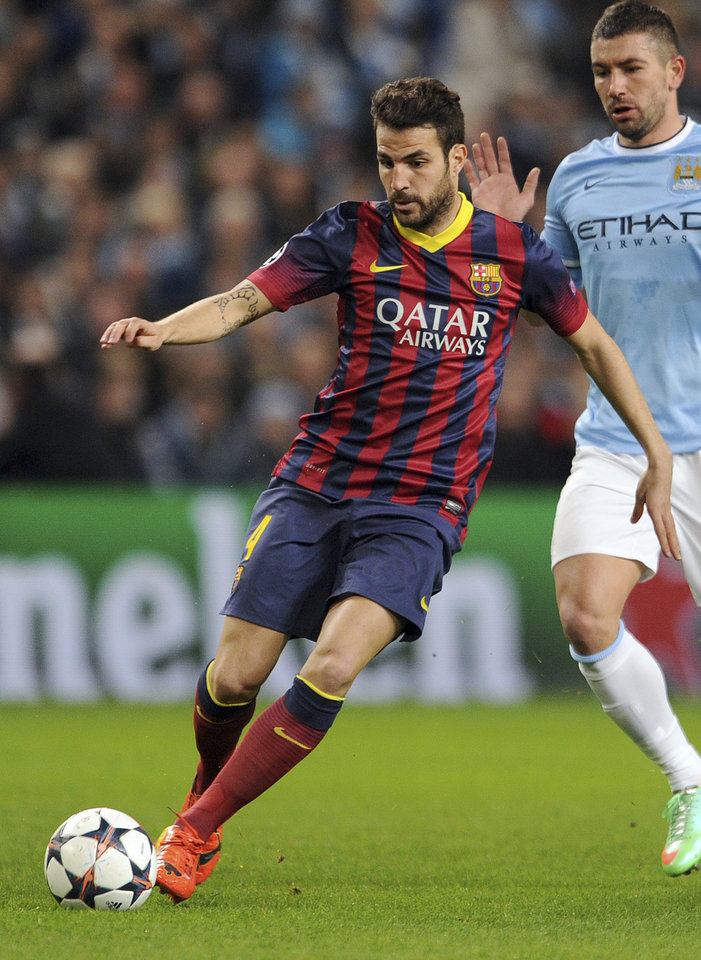 """Photo - FILE - A Tuesday, Feb. 18, 2014 photo from files showing Barcelona's Cesc Fabregas during their Champions League Round of 16 soccer match against Manchester City at the Etihad Stadium in Manchester, England.  Chelsea has announced on its website the signing of Cesc Fabregas from Barcelona on a five-year deal. The 27-year-old Fabregas, who has previously played for Chelsea's London rival Arsenal, says """"I do feel that I have unfinished business in the Premier League"""" and that Chelsea """"match my footballing ambitions with their hunger and desire to win trophies.""""  Fabregas, who is currently with Spain preparing for the World Cup in Brazil, will wear the number four shirt at Chelsea. (AP Photo/Clint Hughes, File)"""