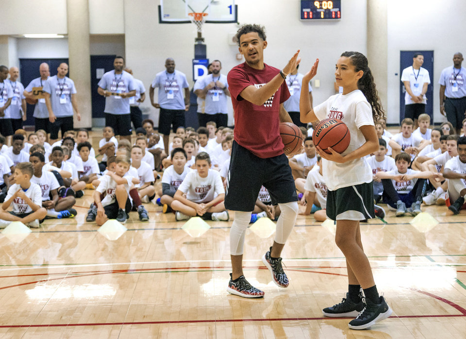Photo -   Trae Young gives a high five to Keeley Parks during the Trae Young Basketball Pro Camp in Norman on Wednesday. [PHOTO BY CHRIS LANDSBERGER, THE OKLAHOMAN]