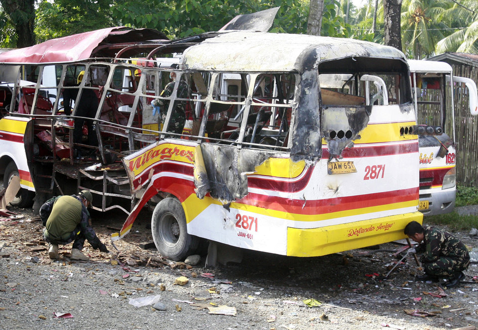 Police and military bomb squad members examine the wreckage of a passenger bus Saturday Sept. 21, 2013 following an explosion Friday evening that killed three people in Zamboanga city in southern Philippines. The explosion occurred as the standoff between Government forces and Muslim rebels, who have taken hostages, continues for the past 13 days Saturday. (AP Photo)