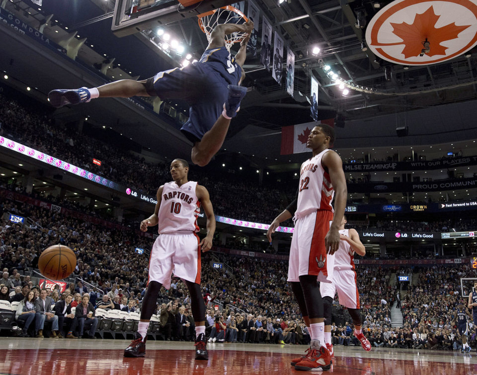 Toronto Raptors forward Rudy Gay (22) and guard DeMar DeRozan (10) react as Memphis Grizzlies guard Tony Allen (9) dunks during the first half of an NBA basketball game, Wednesday, Feb. 20, 2013, in Toronto. (AP Photo/The Canadian Press, Frank Gunn)