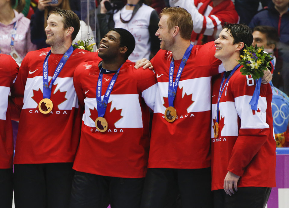 Photo - Canada forward Sidney Crosby, far right, stands with teammates for the Canadian national anthem after beating Sweden 3-0 in the men's gold medal ice hockey game at the 2014 Winter Olympics, Sunday, Feb. 23, 2014, in Sochi, Russia. (AP Photo/Julio Cortez)