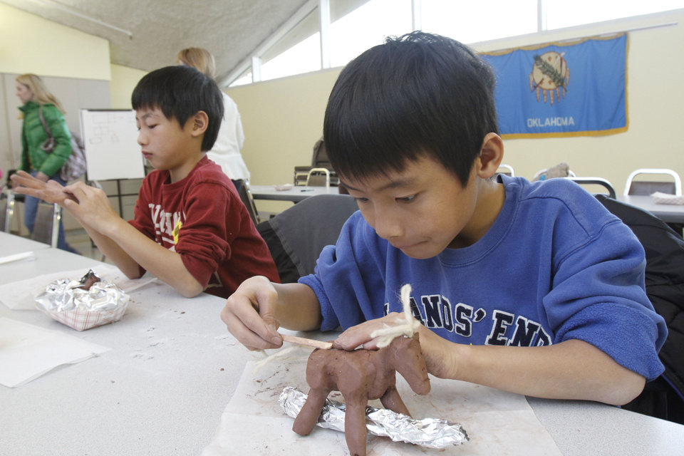9-year-old brothers Nathaniel, front, and Jonathan Chen create clay horses during a sculpture class for kids at the National Cowboy & Western Heritage Museum. Photos By Paul Hellstern, The Oklahoman