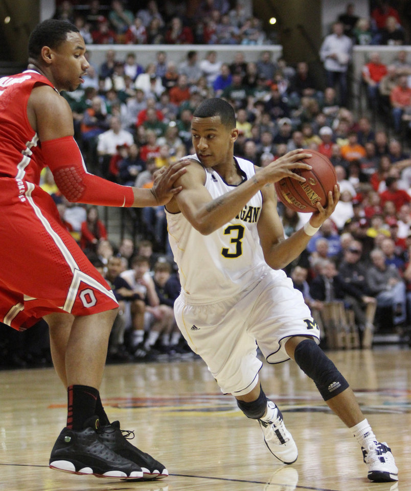 Photo -   Michigan guard Trey Burke (3) drives around Ohio State forward Jared Sullinger in the first half of an NCAA college basketball game in the semifinals of the Big Ten Conference tournament in Indianapolis, Saturday, March 10, 2012. (AP Photo/Kiichiro Sato)