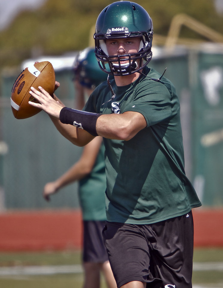 Photo - Edmond Santa Fe quarterback Justice Hansen takes to the field during the first day of football practice at Edmond Santa Fe High School on Tuesday, Aug. 7, 2012, in Edmond, Okla.  Photo by Chris Landsberger, The Oklahoman