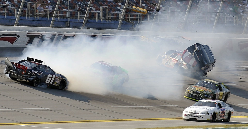 Photo -   Joey Coulter (61) slides backwards as Mark Thompson, top right, climbs over the front of the car of Mike Harmon (31) during a multi-car wreck during the International Motorsports Hall of Fame 250 ARCA auto race at the Talladega Superspeedway in Talladega, Ala., Friday, May 4, 2012. (AP Photo/Rainier Ehrhardt)