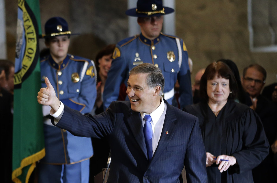 Photo - Jay Inslee, left, gives a thumbs-up after being sworn in as Washington state Governor, Wednesday, Jan. 16, 2013, by Washington Supreme Court Chief Justice Barbara Madsen, right, in the rotunda of the Legislative Building at the Capitol in Olympia, Wash. (AP Photo/Ted S. Warren)