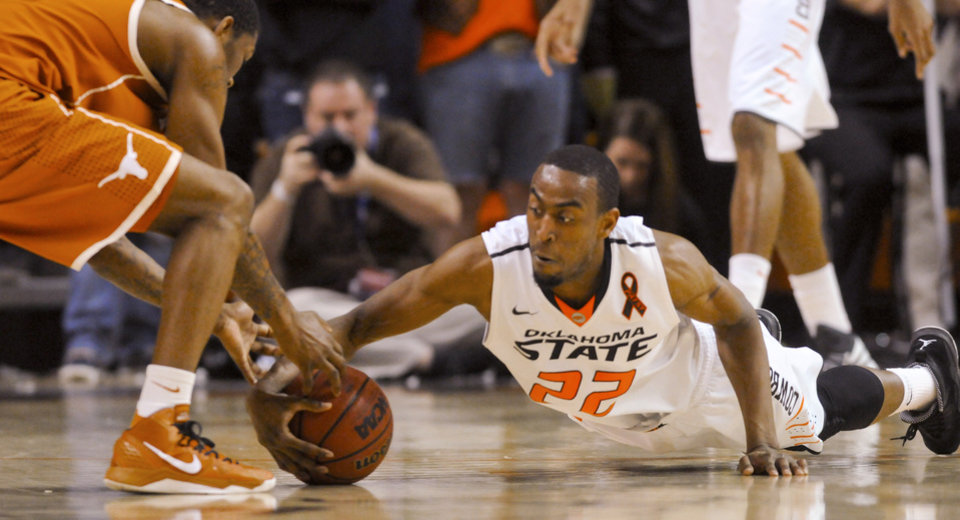 Texas guard Julien Lewis, left, and Oklahoma State guard Markel Brown reach for a loose ball during the second half of an NCAA college basketball game in Stillwater, Okla., Saturday, March 2, 2013. (AP Photo/Brody Schmidt)