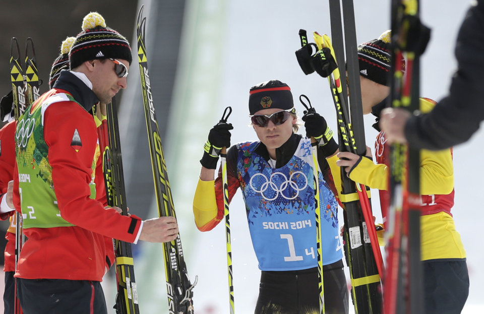 Photo - Germany's Fabian Riessle, center, catches his breath after the German team won the silver after the cross-country portion of the Nordic combined Gundersen large hill team competition at the 2014 Winter Olympics, Thursday, Feb. 20, 2014, in Krasnaya Polyana, Russia. (AP Photo/Matthias Schrader)
