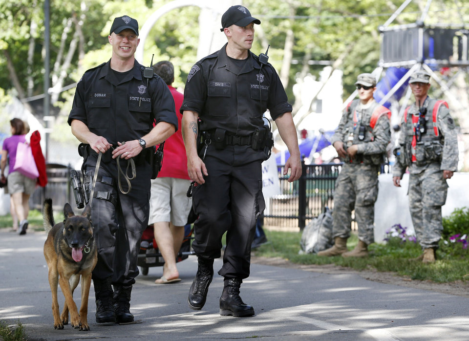 Photo - Massachusetts State Police patrol with a bomb sniffing dog before rehearsal for the Boston Pops Fourth of July concert at the Hatch Shell in Boston, Wednesday, July 3, 2013.    The concert is city's first large public gathering since the Boston Marathon bombings.  (AP Photo/Michael Dwyer)