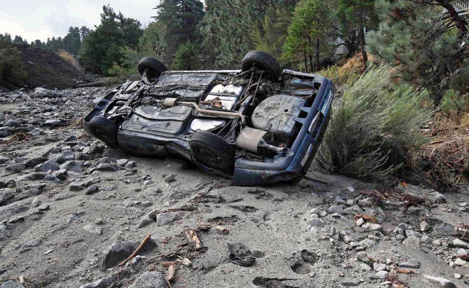 Photo - A car lies where it was swept down a wash in the mountain community of Forest Falls in the San Bernardino Mountains Monday, Aug. 4, 2014. Crews cleared roads in an area where some 2,500 had been stranded after thunderstorms caused mountain mudslides in Southern California over the weekend, while authorities estimated that between 6 and 8 homes were badly damaged and likely uninhabitable. One person was found dead in a vehicle that was caught in a flash flood. A group of campers spent the night at a community center near Forest Falls headed. (AP Photo/Nick Ut)