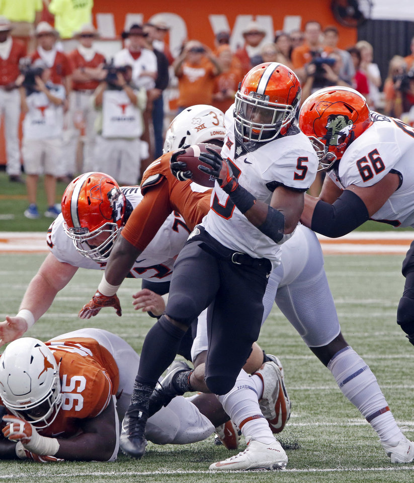 Photo - Oklahoma State running back Justice Hill (5) runs the ball during the second half of an NCAA college football game against Texas, Saturday, Oct. 21, 2017, in Austin, Texas. Oklahoma State won 13-10 in overtime. (AP Photo/Michael Thomas)