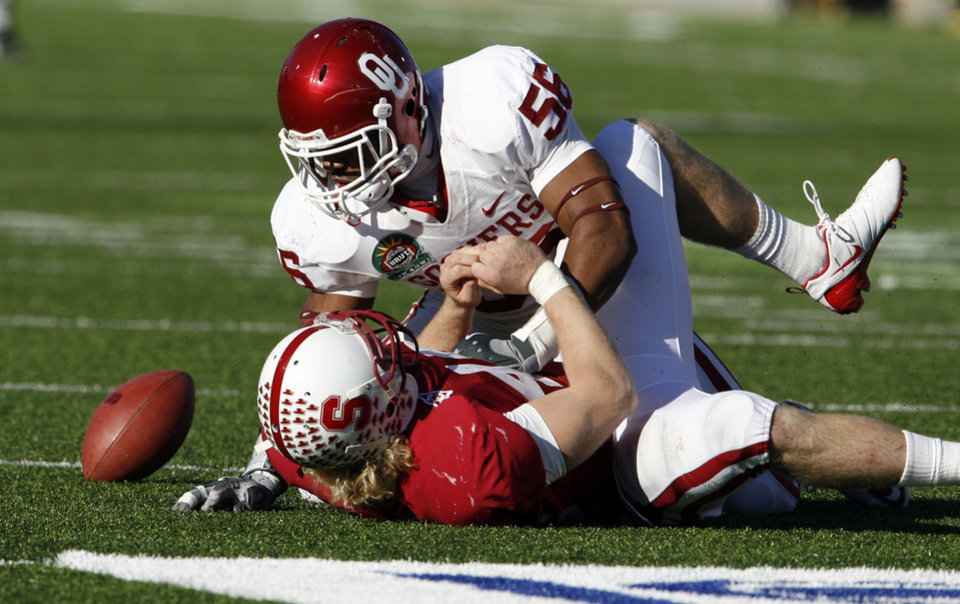 Photo - Ronnell Lewis (56) disrupts a pass intended for Owen Marecic (48) during the second half of the Brut Sun Bowl college football game between the University of Oklahoma Sooners (OU) and the Stanford University Cardinal on Thursday, Dec. 31, 2009, in El Paso, Tex.   Photo by Steve Sisney, The Oklahoman