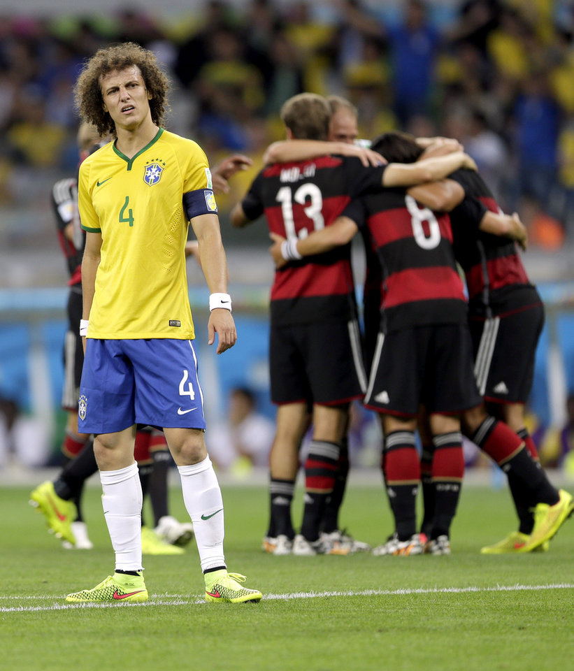 Photo - Brazil's David Luiz (4) reacts after Germany's Sami Khedira scored his side's fifth goal during the World Cup semifinal soccer match between Brazil and Germany at the Mineirao Stadium in Belo Horizonte, Brazil, Tuesday, July 8, 2014. (AP Photo/Andre Penner)