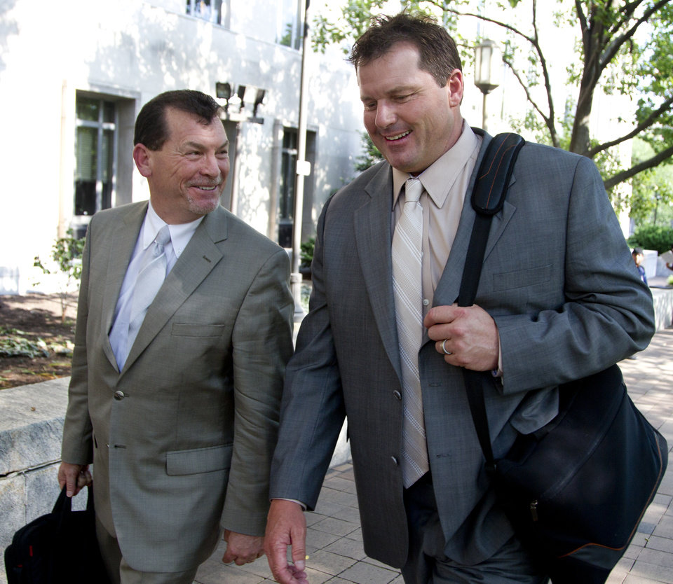 Photo -   Former Major League Baseball pitcher Roger Clemens, right, with a member of his legal team, leaves federal court in Washington, Friday, May 25, 2012. A forensic scientist testified Friday that two cotton balls and a syringe needle allegedly saved after a steroids injection, tested positive for Roger Clemens' DNA, a key moment as the government tries to prove the former pitcher used performance-enhancing drugs. (AP Photo/Manuel Balce Ceneta)