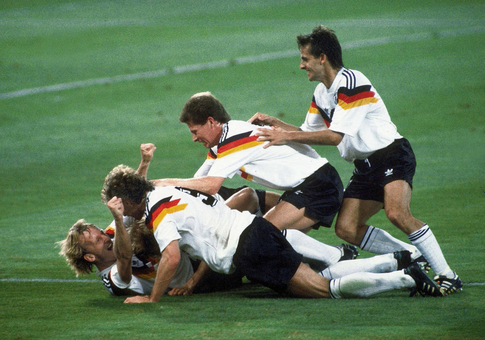 Photo - FILE - In this July 8, 1990 file photo, Germany players celebrate after Andreas Brehme, left on ground, scores the winning goal in the World Cup soccer final match against Argentina, in the Olympic Stadium, in Rome, Italy. On this day: Germany defeats Argentina 1-0 to win the World Cup in a final that also saw two Argentine players sent off. (AP Photo/Carlo Fumagalli, File)