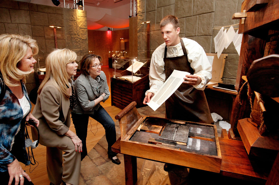 Docent Chris Griffin, playing the part of a printer, shows a page he just printed on this replica of the Guttenberg press to Vickie Weigel, Dandy Price and Nycke White, from left. Next week, visitors to the Oklahoma City Museum of Art will have the opportunity to view the world premiere of the traveling exhibition of rare biblical texts and assorted artifacts in an interactive, multimedia exhibit called Passages.  The 14.000 square foot exhibit celebrates the 400th anniversary of the King James Bible and it features nearly 300 objects  from the Green Collection, one of the world's largest private collections of rare biblical texts and artifacts.  Members of the media were given a preview on Friday, May 13,  2011,   Photo by Jim Beckel, The Oklahoman
