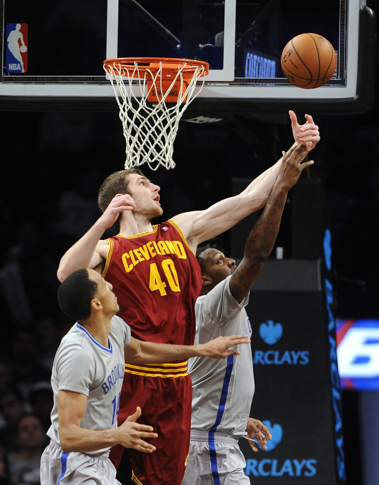 Photo - Brooklyn Nets' Shaun Livingston (14) and Andray Blatche, right, vie for a rebound with Cleveland Cavaliers' Tyler Zeller (40) during the first half of an NBA basketball game Friday, March 28, 2014, in New York. (AP Photo/Kathy Kmonicek)