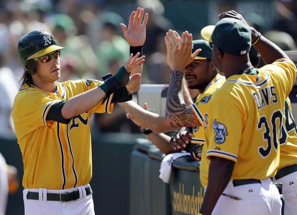 Oakland Athletics\' Josh Reddick, left, receives high-fives after scoring on a single from Seth Smith during the fourth inning of a baseball game against the Texas Rangers on Wednesday, Oct. 3, 2012, in Oakland, Calif. (AP Photo/Marcio Jose Sanchez)