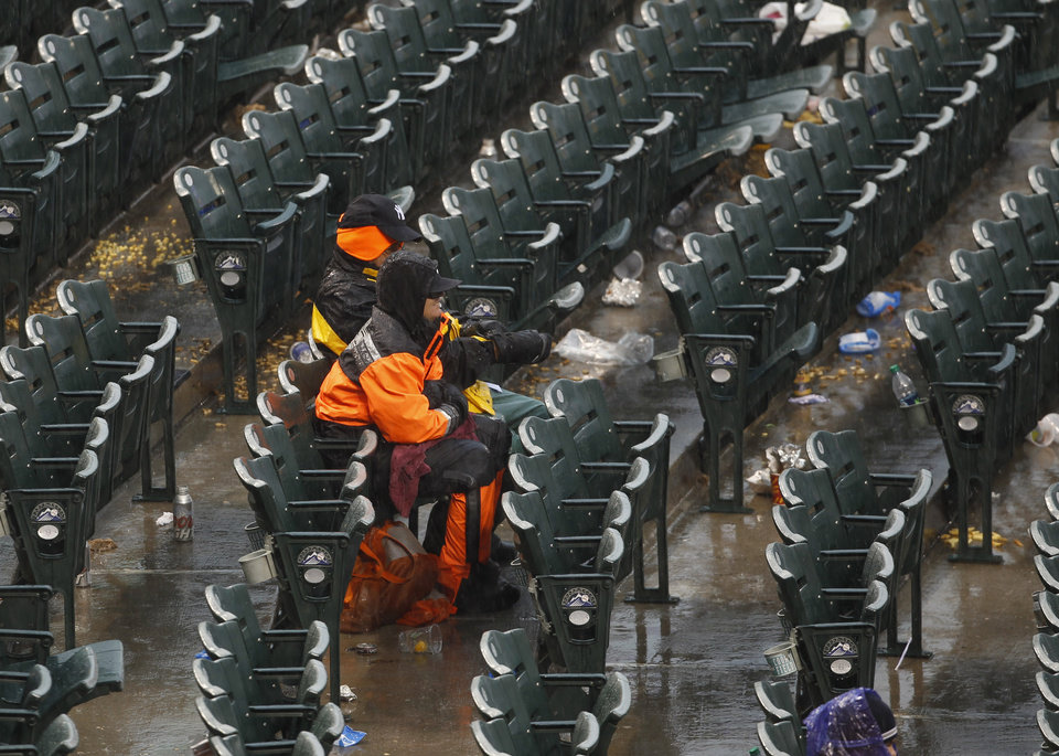 Photo - A pair of fans sits through the second rain delay at Coors Field as play was suspended in the fourth inning of a baseball game between the New York Yankees and Colorado Rockies in Denver, Thursday, May 9, 2013. (AP Photo/David Zalubowski)