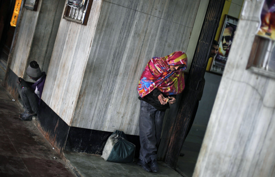 An Indian man wrapped in a blanket takes shelter at the entrance to a cinema hall as it rains in New Delhi, India, Tuesday, Feb. 5, 2013. Heavy rains accompanied by a thunderstorm lashed the capital for the second day Tuesday throwing traffic out of gear across the city. (AP Photo/Altaf Qadri)