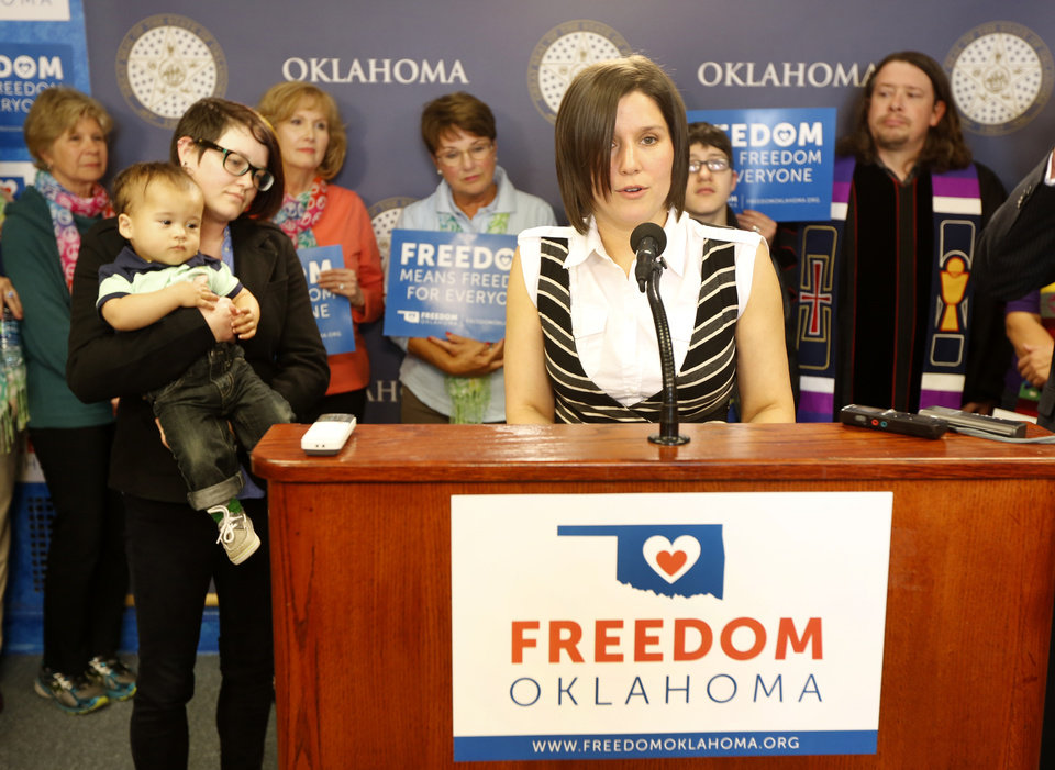 Photo -  Freedom Oklahoma Steve Gooch The Oklahoman The Oklahoman  Rebeka Radcliff speaks during a Freedom Oklahoma news conference as her partner, Kim McDonald, left, holds their son, Jordan, 13 months, Tuesday at the state Capitol in Oklahoma City. Freedom Oklahoma is a coalition that calls for marriage equality.  Photo By Steve Gooch, The Oklahoman   Steve Gooch