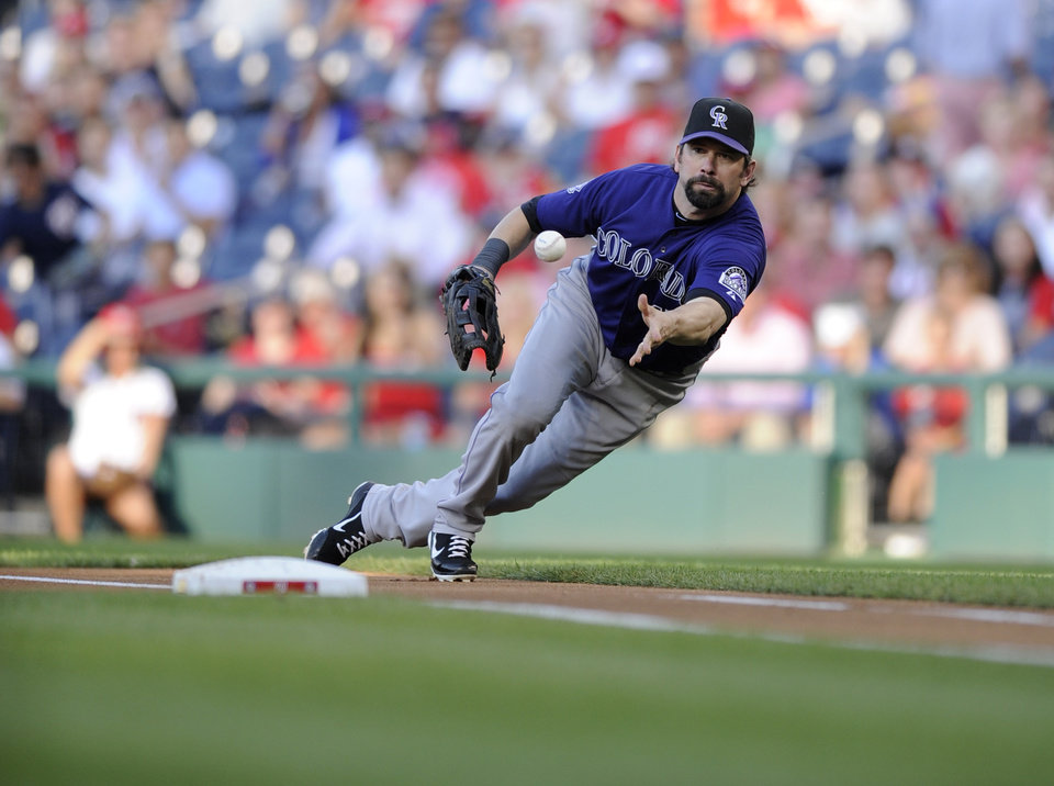 Photo - Colorado Rockies first baseman Todd Helton tosses the ball to Tyler Chatwood, not seen, to get out Washington Nationals' Denard Span out at first on a grounder during the first inning of a baseball game, Friday, June 21, 2013, in Washington. (AP Photo/Nick Wass)