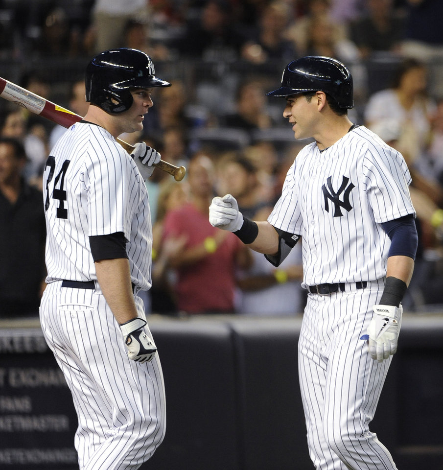 Photo - New York Yankees' Brian McCann (34) greets Jacoby Ellsbury after Ellsbury hit a two-run home run off Cincinnati Reds starting pitcher Mike Leakein the fifth inning of an interleague baseball game at Yankee Stadium on Friday, July 18, 2014, in New York. (AP Photo/Kathy Kmonicek)