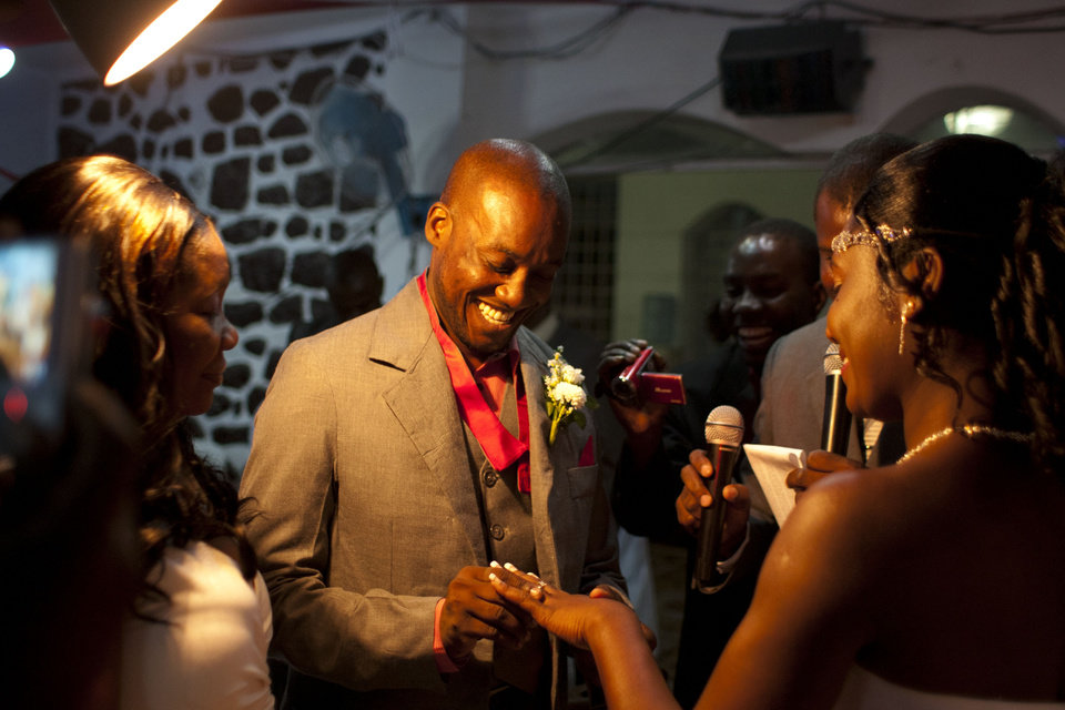 Photo - In this July 20, 2012 photo, professional dancer Georges Exantus puts a ring on the finger of his bride Sherly Henrisme Exantus at their wedding in Port-au-Prince, Haiti. Exantus thought he'd never dance again. The earthquake three years ago in Haiti's capital flattened the apartment where he was living, where he spent three days trapped under a heap of jagged rubble. After friends dug him out, doctors amputated his right leg just below the knee. Three years later, the 32-year-old professional dancer is back on the floor, spinning away as he does the salsa, cha-cha and samba. A prosthetic leg doesn't hold him back. Exantus says he's the same person he was before the Jan. 12, 2010, earthquake struck southern Haiti. (AP Photo/Dieu Nalio Chery)