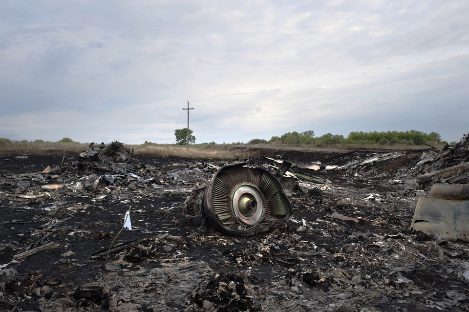 Photo - The crash site of a Malaysia Airlines jet is pictured near the village of Hrabove, eastern Ukraine, early Saturday, July 19, 2014. World leaders demanded Friday that pro-Russia rebels who control the eastern Ukraine crash site of Malaysia Airlines Flight 17 give immediate, unfettered access to independent investigators to determine who shot down the plane. (AP Photo/Evgeniy Maloletka)