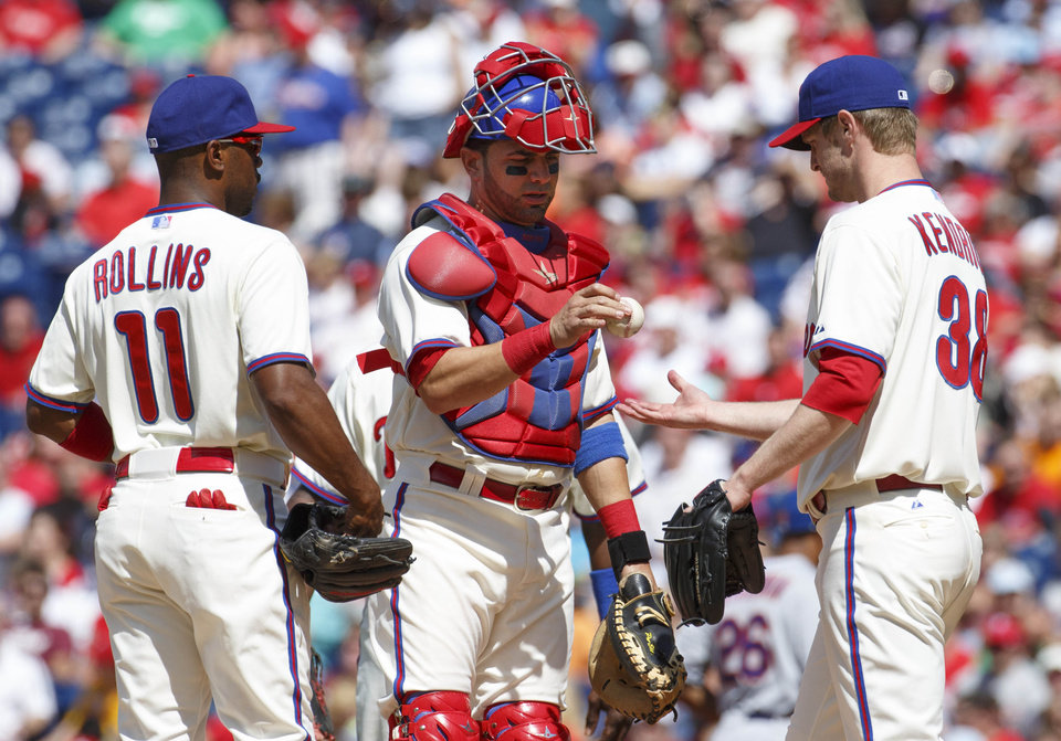 Photo - Philadelphia Phillies starting pitcher Kyle Kendrick, right, gets the ball back from catcher Wil Nieves, center, after giving up the second run to the New York Mets during the first inning of a baseball game, Saturday, May 31, 2014, in Philadelphia. (AP Photo/Chris Szagola)