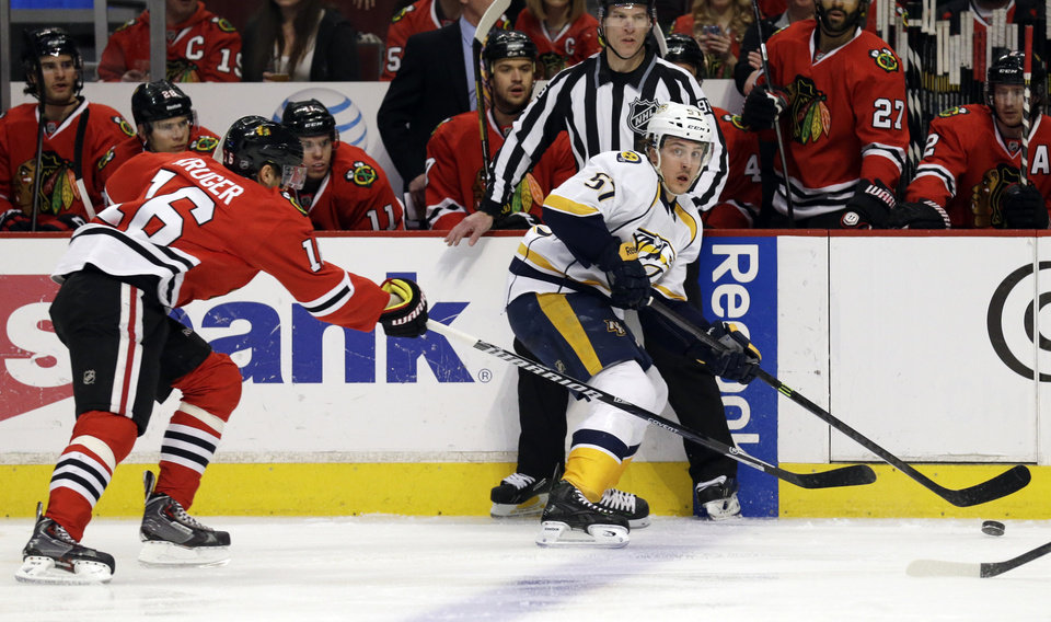 Photo - Nashville Predators' Gabriel Bourque (57), right, looks to a pass against Chicago Blackhawks' Marcus Kruger (16)  during the first period of an NHL hockey game in Chicago, Sunday, March 23, 2014. (AP Photo/Nam Y. Huh)