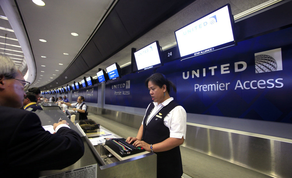 Photo - FILE - In this Wednesday, July 13, 2011, file photo, ticket agent Dee Manzon helps a customer at United Airlines premier access check-in counter at San Francisco International Airport in San Francisco. United Airlines said Thursday, Jan. 16, 2014 it will furlough 688 flight attendants after it didn't get enough people to take a voluntary buyout. United has said it wants to cut $2 billion in annual expenses. (AP Photo/Eric Risberg, File)