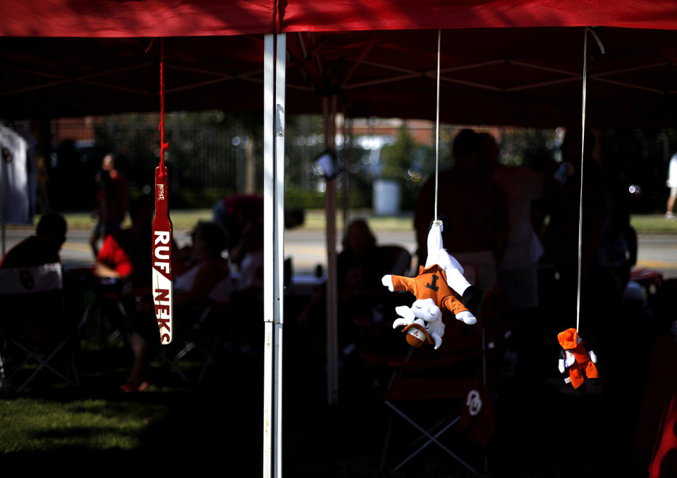 Photo - Decorations hang from a canopy as fans tailgate before a college football game between the University of Oklahoma Sooners (OU) and the West Virginia University Mountaineers at Gaylord Family-Oklahoma Memorial Stadium in Norman, Okla., on Saturday, Sept. 7, 2013. Photo by Bryan Terry, The Oklahoman