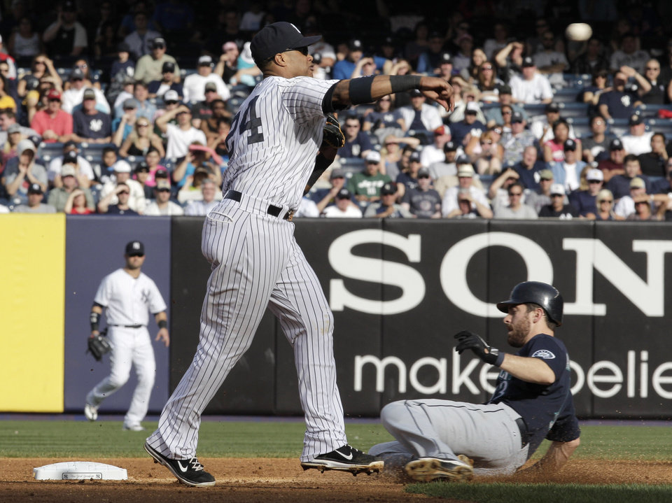 Seattle Mariners Dustin Ackley is out at second base as New York Yankees Robinson Cano throws to first base to complete a double play in the sixth inning of a baseball game on Saturday, May 12, 2012 in New York. The Yankees won 6-2. (AP Photo/Peter Morgan)