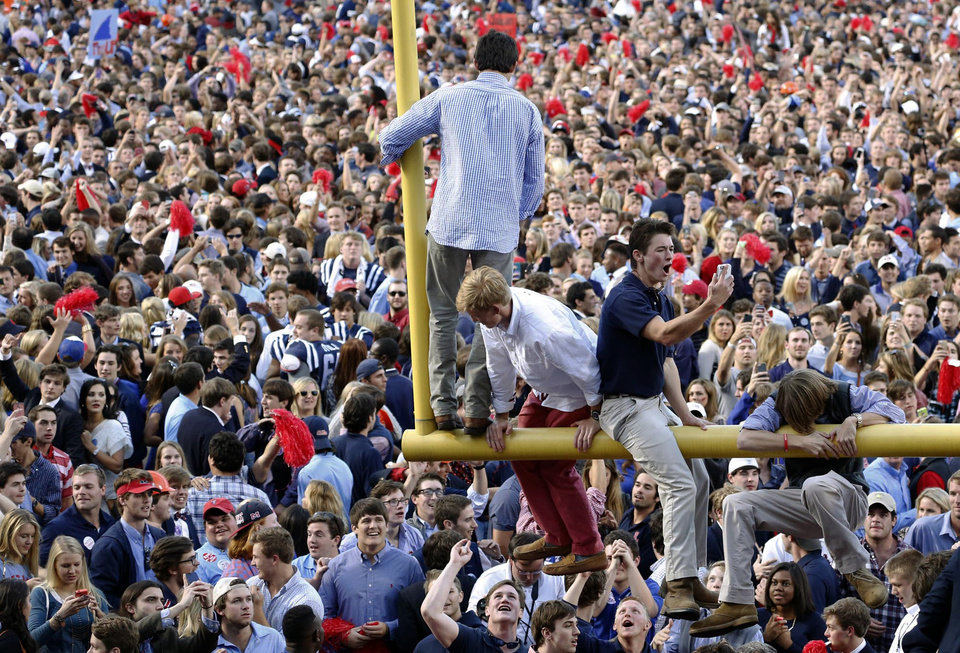 Photo - Mississippi fans gather on the field, with a few on a goal post, after Mississippi defeated Alabama 23-17 in an NCAA college football game in Oxford, Miss., on Saturday Oct. 4, 2014. (AP Photo/Tuscaloosa News, Robert Sutton)