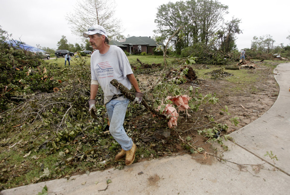 Mark Sarlo drags a branch to the street in the Dripping Springs Estates Saturday, May 15, 2010. Saturday hundreds of volunteers went into areas that had been affected by last week's tornadoes to help clear debris. Photo by Doug Hoke, The Oklahoman.
