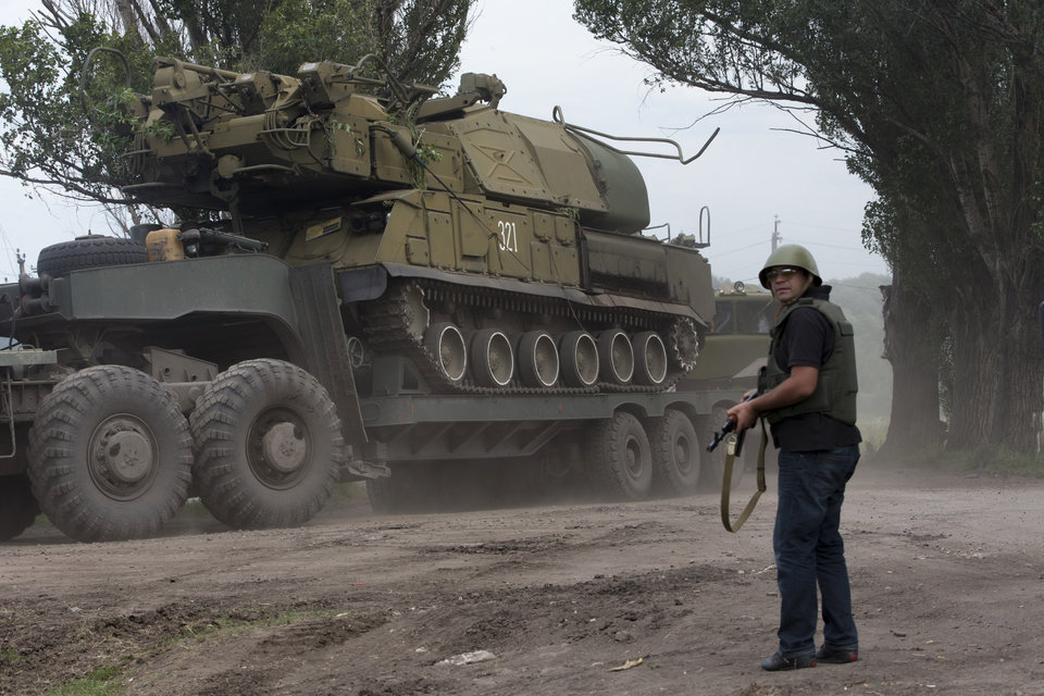 Photo - Ukrainian government forces maneuver antiaircraft missile launchers Buk as they are transported north-west from Slavyansk, eastern Ukraine Friday, July 4, 2014. (AP Photo/Dmitry Lovetsky)