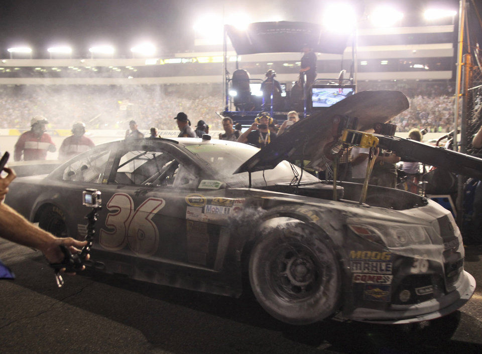 Photo - Reed Sorenson's car is towed to the garage area after a fire during the NASCAR Sprint Cup auto race at Richmond International Raceway in Richmond, Va., Saturday, April 26, 2014. (AP Photo/Zach Gibson)