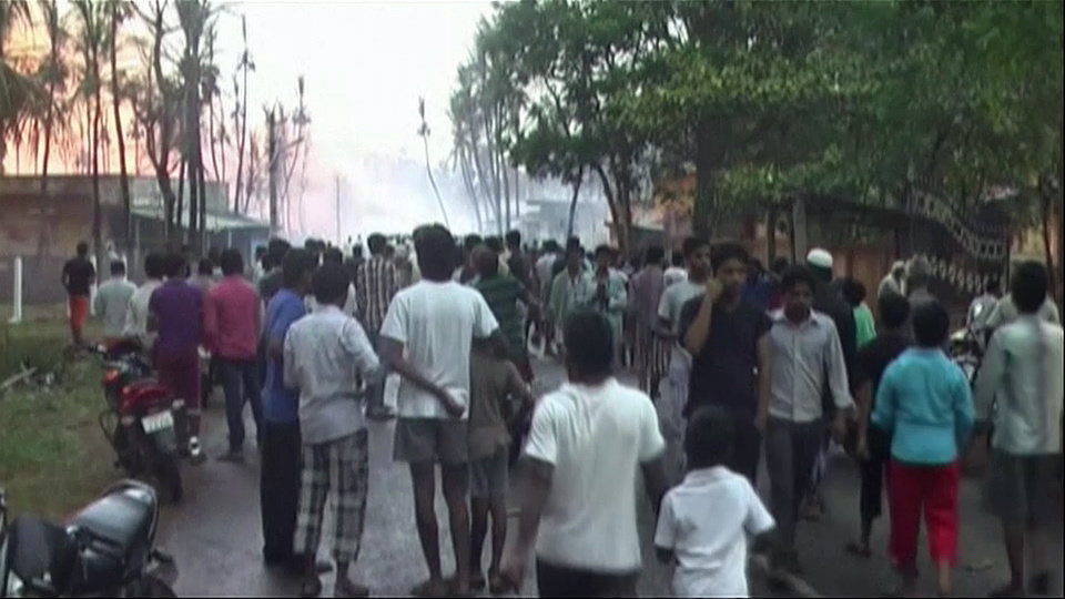 Photo - In this image taken from video, people gather on a street in Nagaram village, in the southern Indian state of Andhra Pradesh after a state-owned gas pipeline exploded Friday, June 27, 2014. A top official of the state-run Gas Authority of India Ltd, said more than a dozen people died in the fire following the explosion in the pipeline. (AP Photo/NNIS via AP Video) INDIA OUT