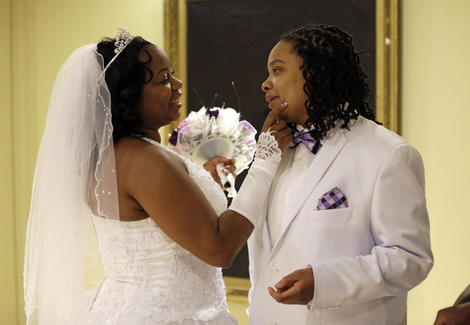 Photo - Darcia Anthony, left, and her partner, Danielle Williams, chat before participating in a marriage ceremony at City Hall in Baltimore, Tuesday, Jan. 1, 2013. Same-sex couples in Maryland are now legally permitted to marry under a new law that went into effect after midnight on Tuesday. Maryland is the first state south of the Mason-Dixon Line to approve same-sex marriage. (AP Photo/Patrick Semansky)