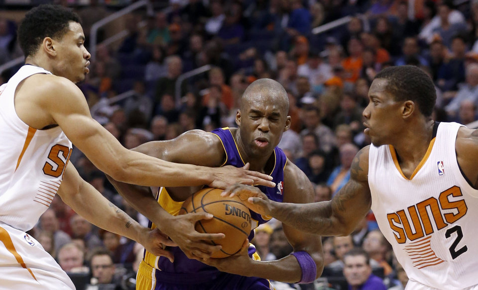 Los Angeles Lakers' Jodie Meeks gets tied up by Phoenix Suns' Eric Bledsoe (2) and Gerald Green, left, during the first half of an NBA basketball game Monday, Dec. 23, 2013, in Phoenix. (AP Photo/Ross D. Franklin)