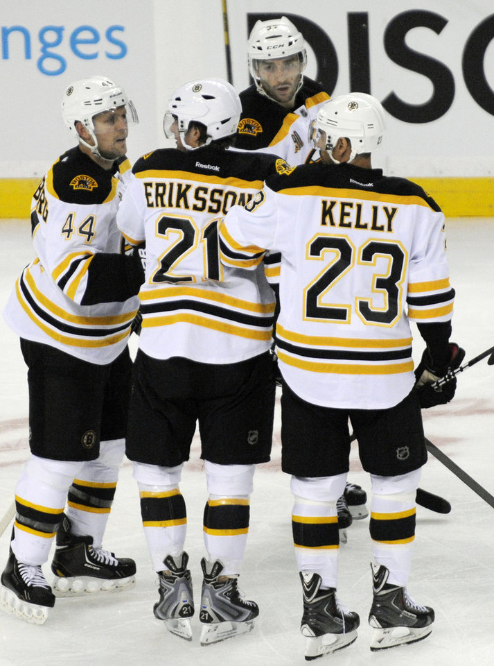 Photo - Boston Bruins' Loui Eriksson (21), of Sweden, is helped off the ice by Bruins' Dennis Seidenberg (44), and Chris Kelly (23) after a hit to the head by Buffalo Sabres' John Scott during the third period of an NHL hockey game in Buffalo, N.Y., Wednesday, Oct. 23, 2013.Boston won 5-2. (AP Photo/Gary Wiepert)